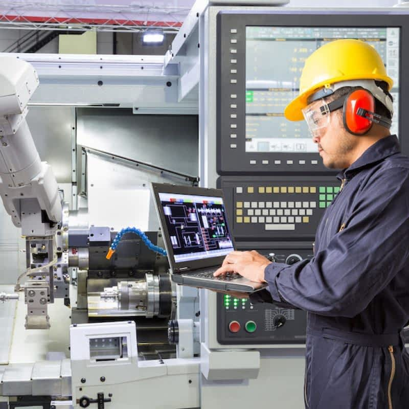 Engineer using laptop computer for maintenance automatic robotic arm with CNC machine in smart factory. Industry 4.0 concept
