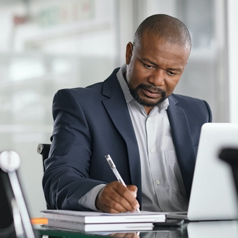 African serious businessman writing notes and using laptop. Mature business man writing his strategy on notebook while using laptop in modern office. Focused black entrepreneur sitting at desk in modern office while working.